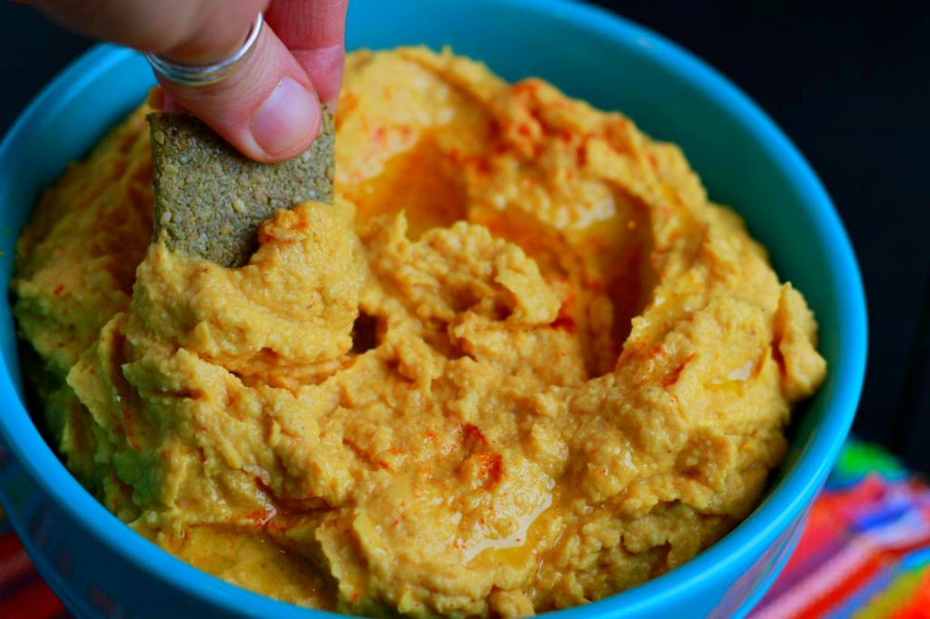 hand dipping a chip into hummus in blue bowl