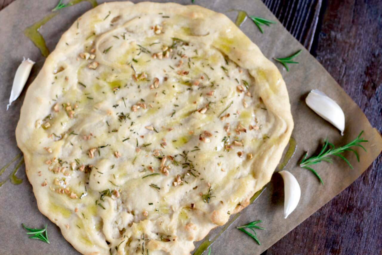 a round flatbread with rosemary and garlic on top