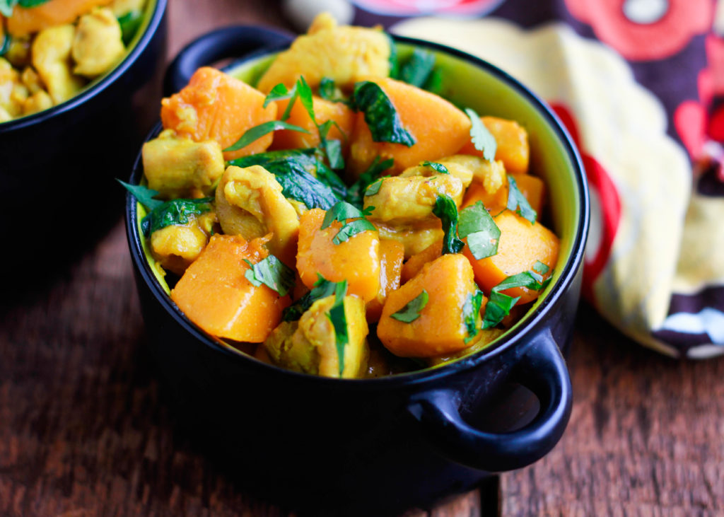 chicken pumpkin curry in a black bowl