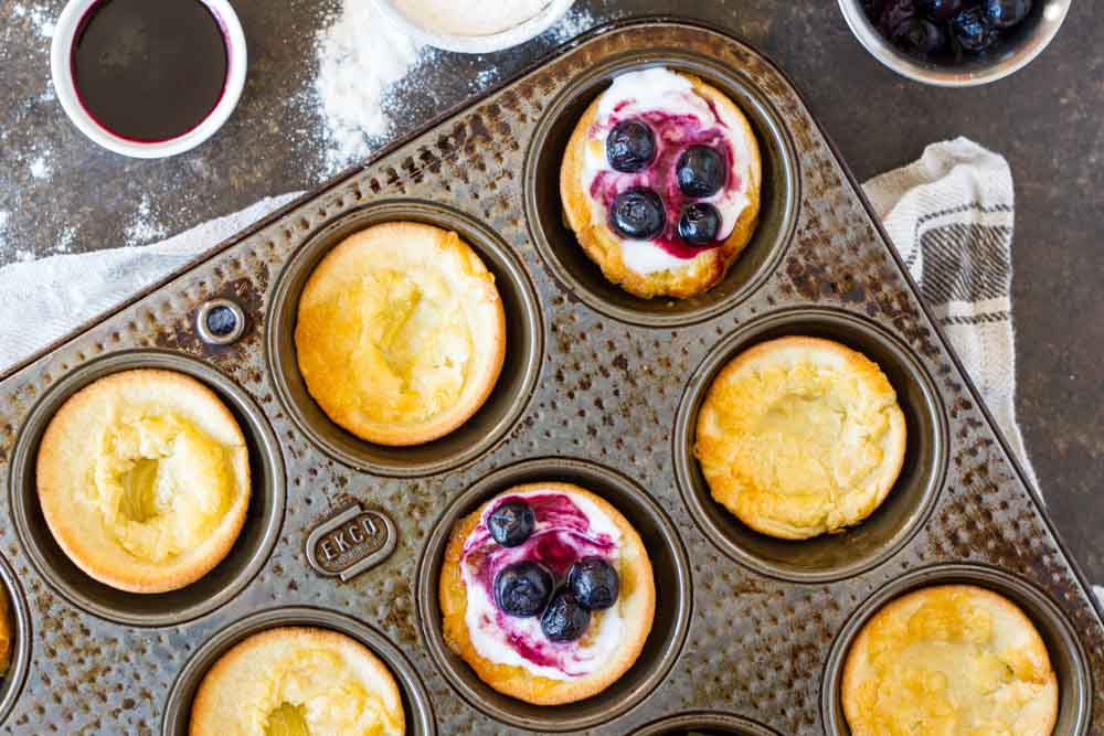 Mini Dutch Babies (gluten free, nut free, paleo) in muffin tins with blueberries