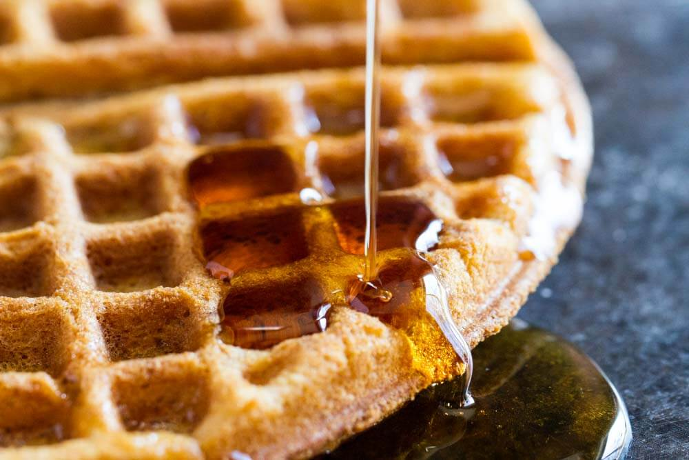 maple syrup pouring on a gluten free waffle