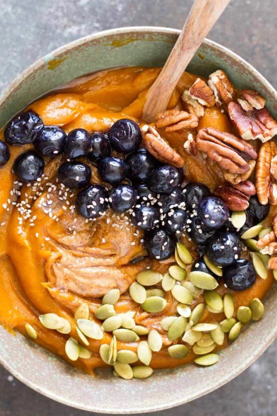 green bowl with sweet potatoes, nuts, seeds, and blueberries in it