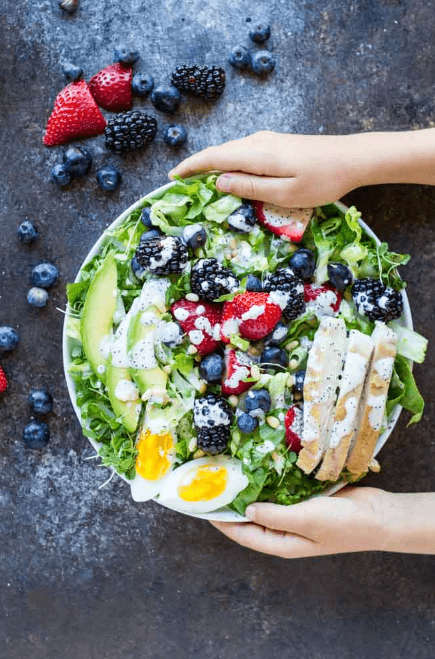 hands holding white plate with berry avocado chicken salad