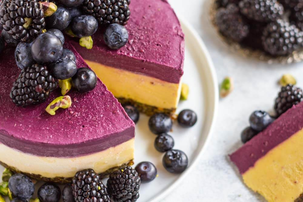 Mango Blackberry Cheesecake with slice cut out of it
