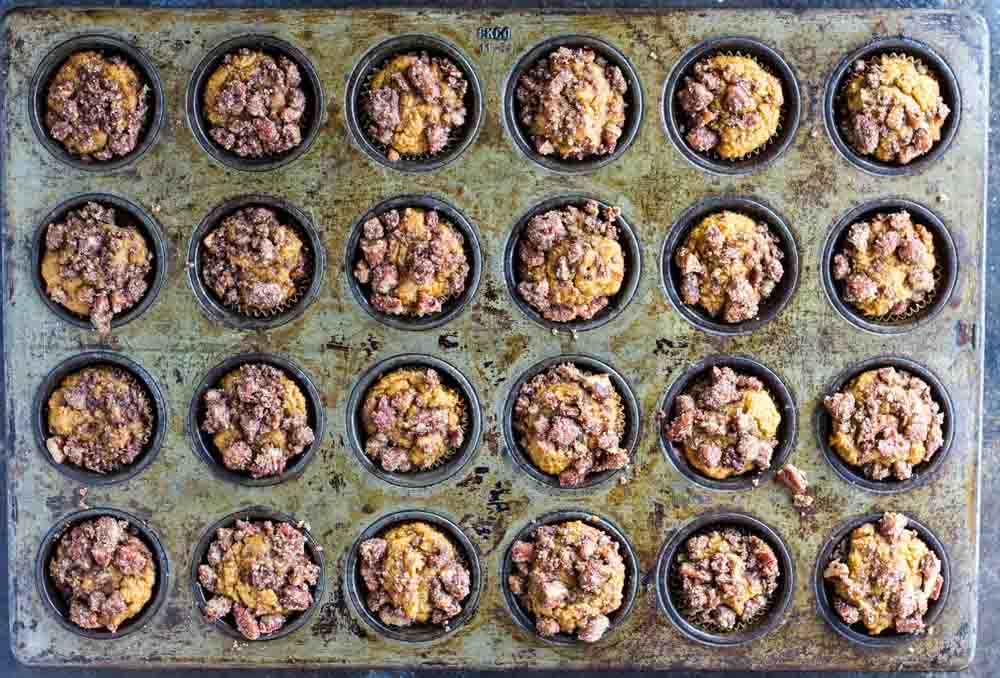 twenty four Mini Pumpkin Muffins in a baking tin