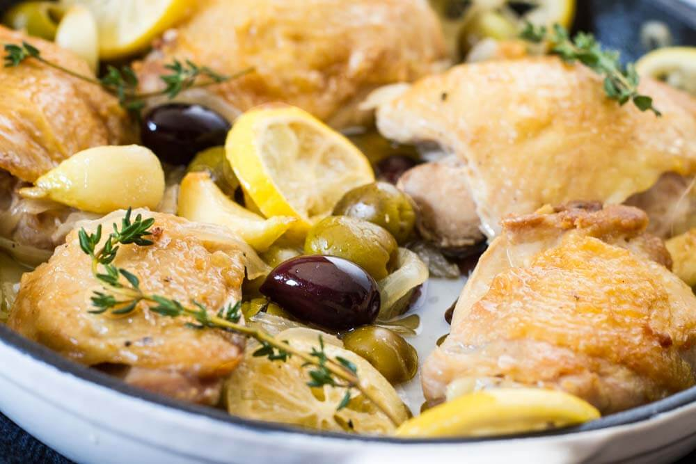 Braised Chicken thighs with lemons and olives in a white skillet