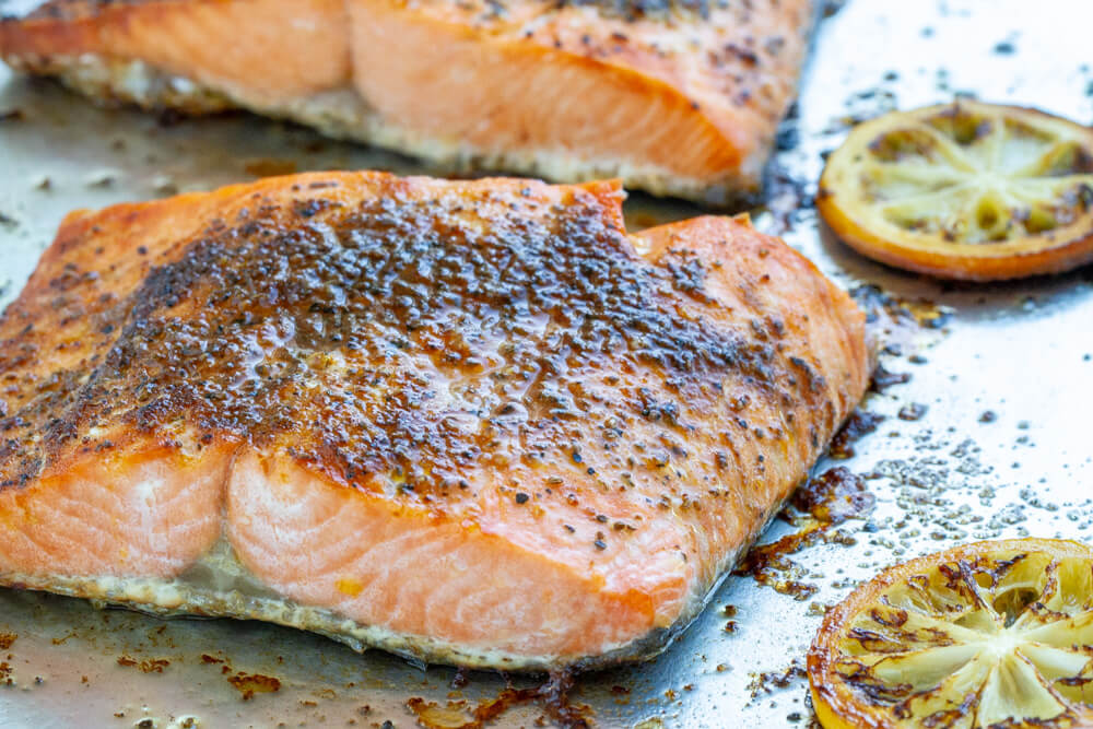Broiled Salmon on baking sheet with lemons