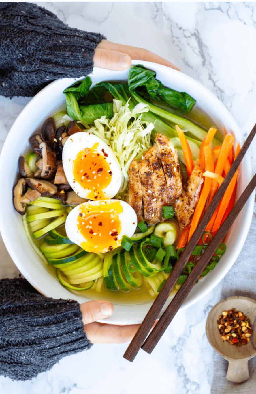 hands holding white bowl with ramen in it