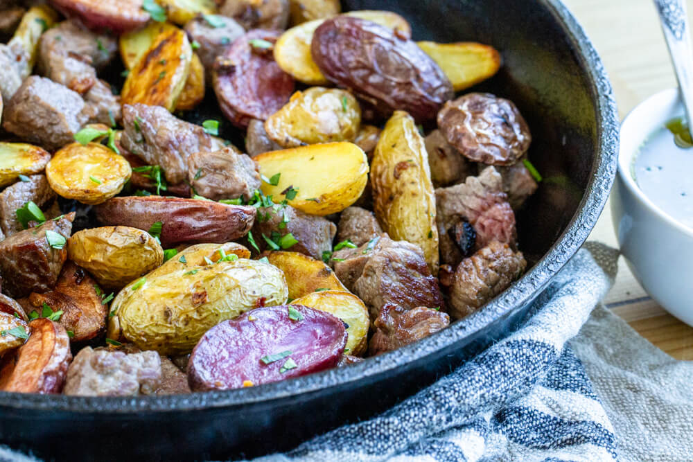 Steak Bites with Garlicky Potatoes in black cast iron skillet