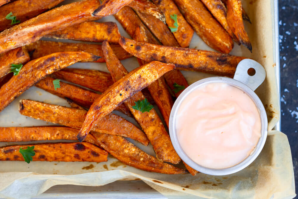 Sweet Potato Fries with Sriracha Mayo on parchment paper