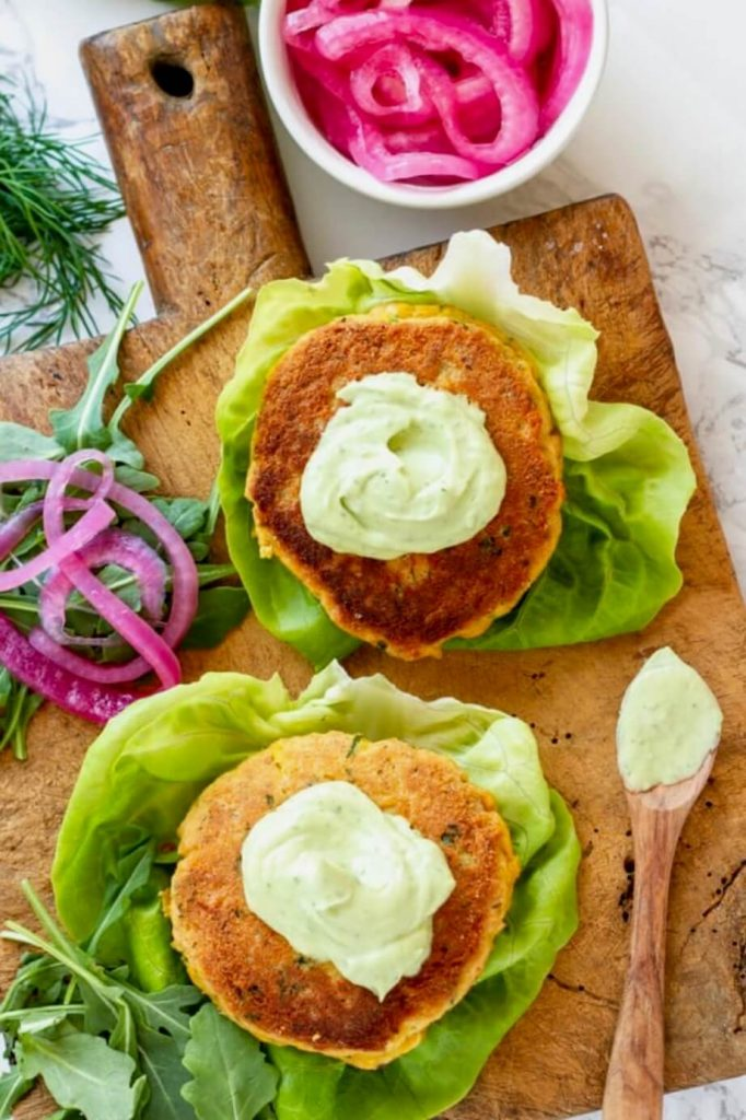 two salmon burgers on a cutting board with green sauce on top