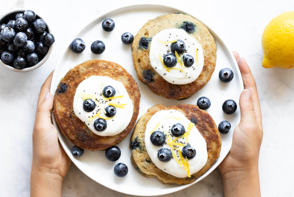 hands holding white plate with pancakes
