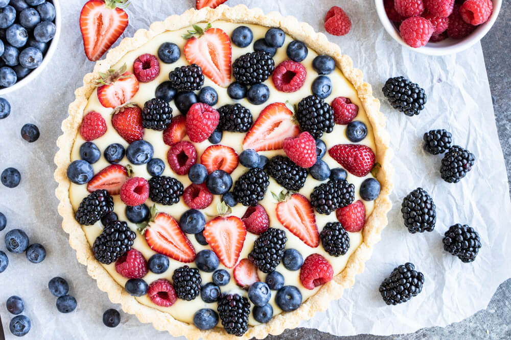 Gluten free Fruit Tart on white parchment paper surrounded by berries