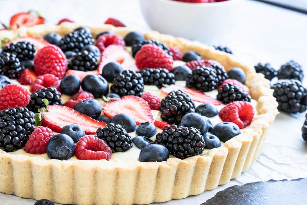 summer berries sitting on creamy custard tart