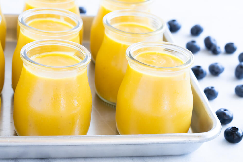 small glass jars filled with mango pudding