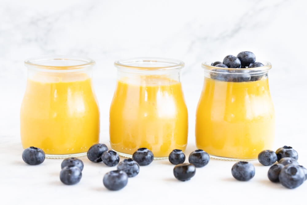 three glass jars of mango pudding in a row