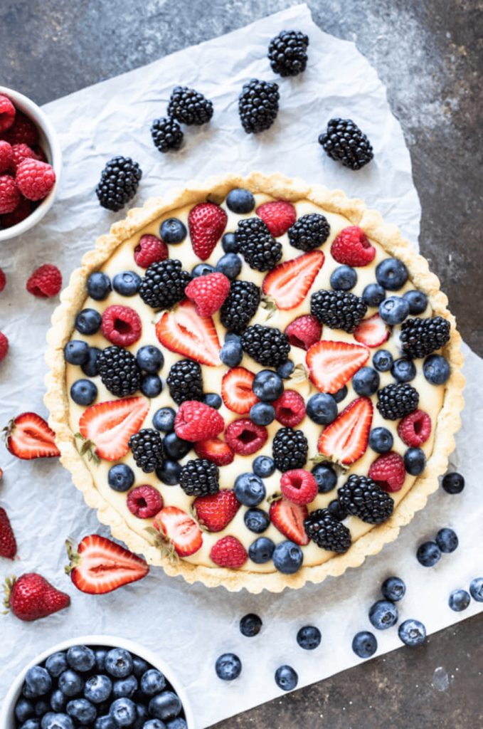 fruit tart with summer berries on top of parchment paper