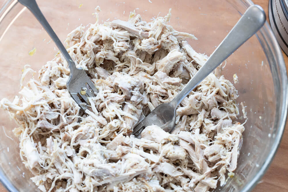 bowl of shredded chicken with two forks