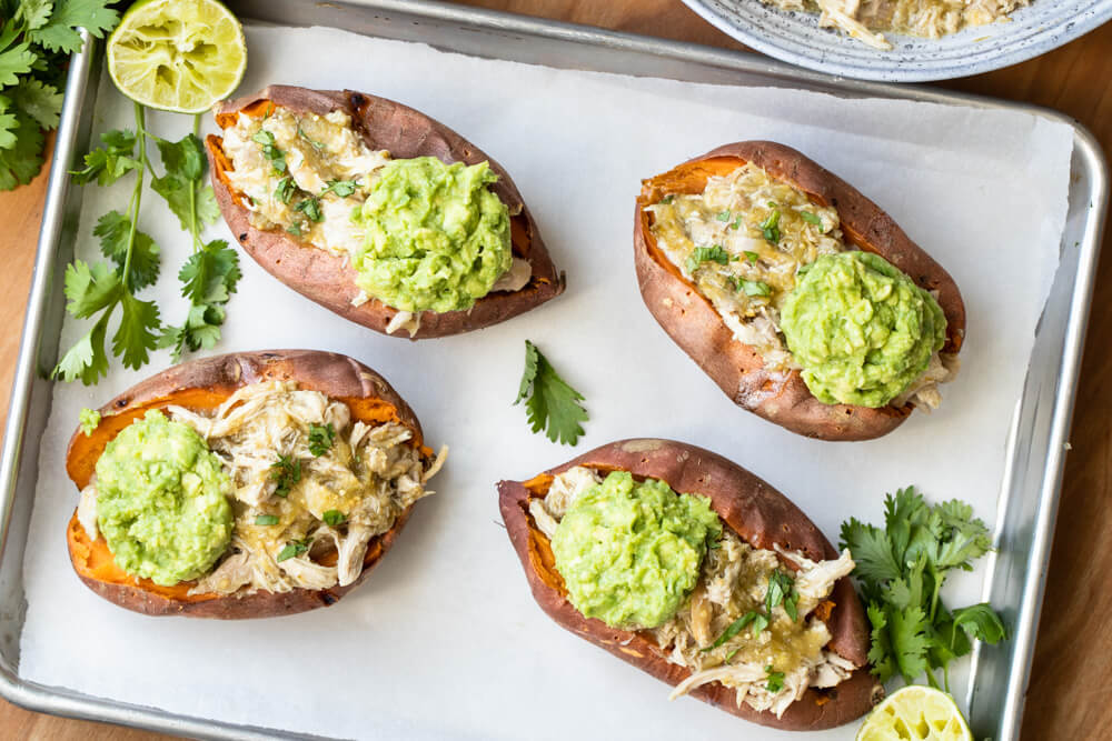 four salsa verde chicken stuffed sweet potatoes on baking sheet