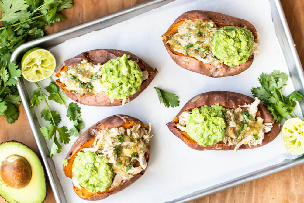 baking pan with four salsa verde stuffed sweet potatoes