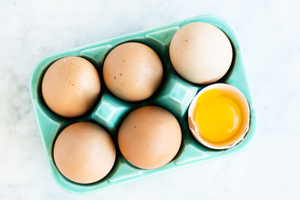 six eggs in a green carton