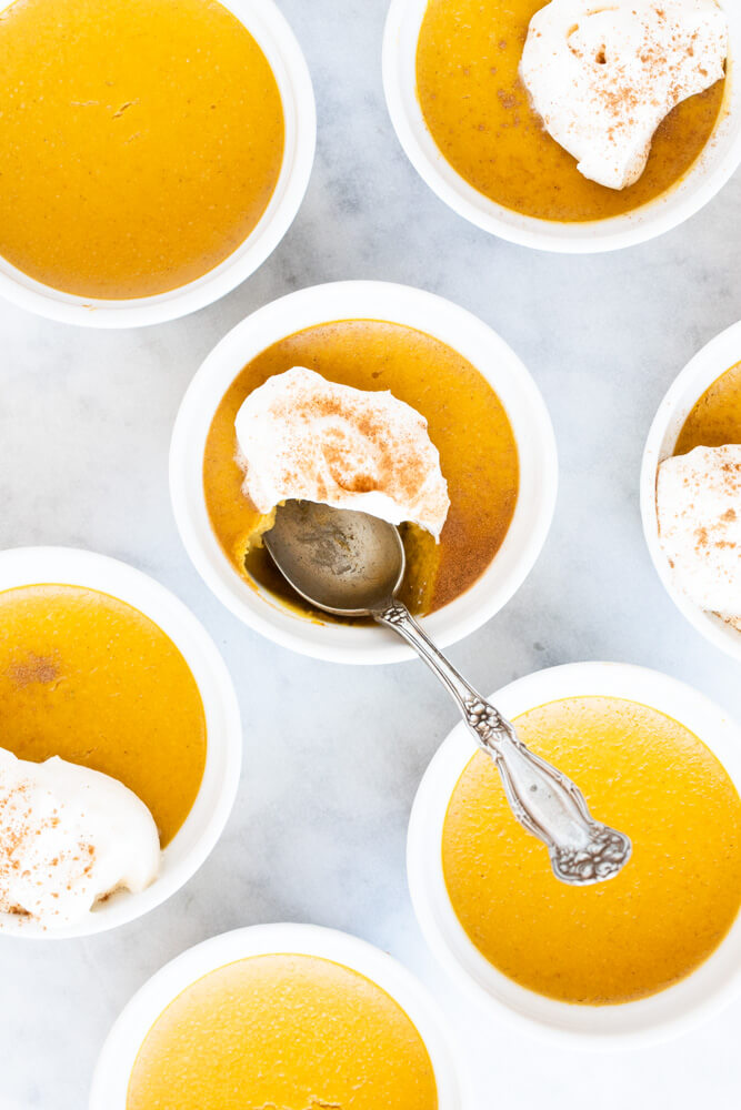 close up of white ramekin with pumpkin custard
