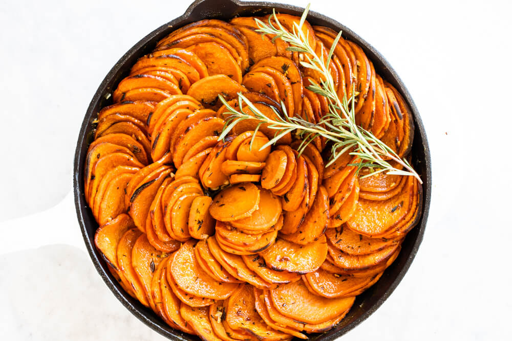 garlic and herb sweet potatoes in white skillet