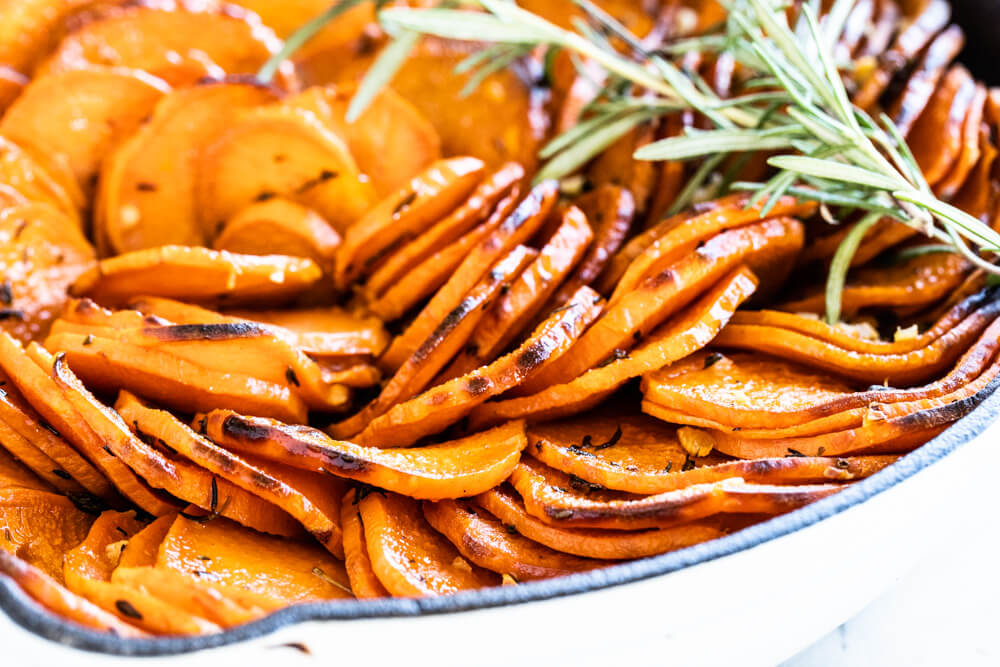 close up of sweet potato slices in white skillet