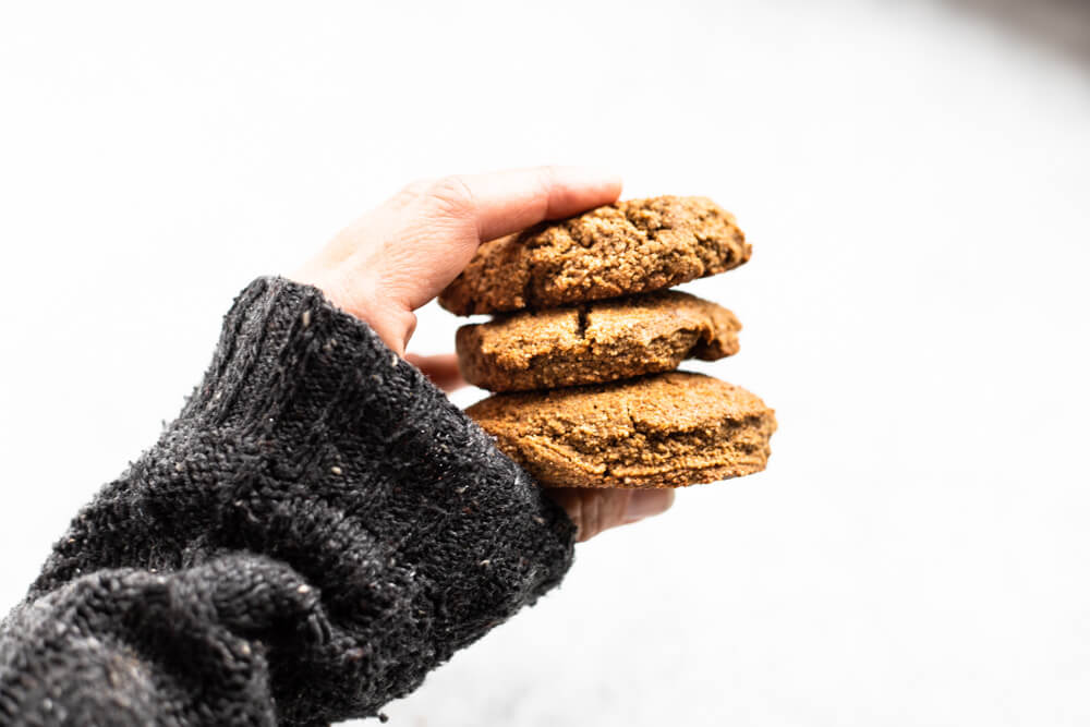 hand with grey sweater holding three cookies