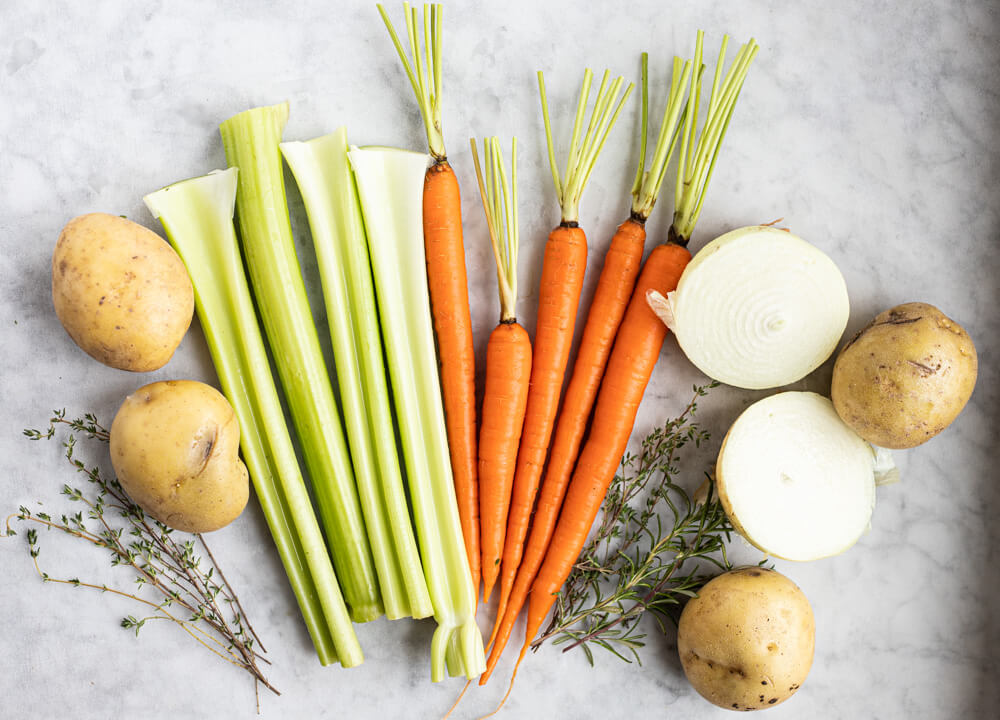 potatoes, carrots, and celery on marble counter