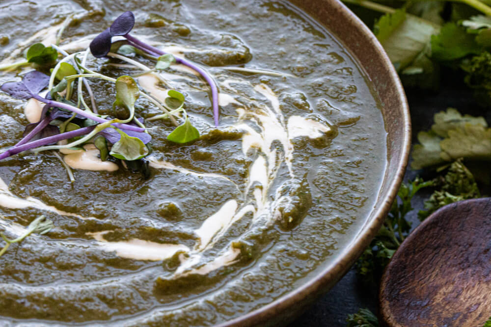 green soup in green bowl with cream on top