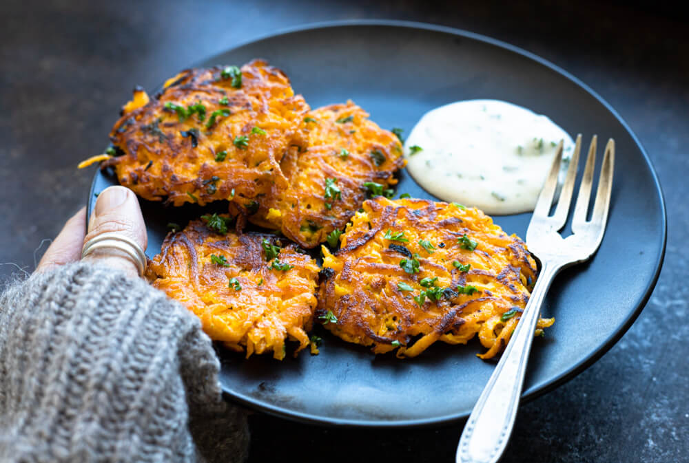hand holding black plate with butternut squash fritters