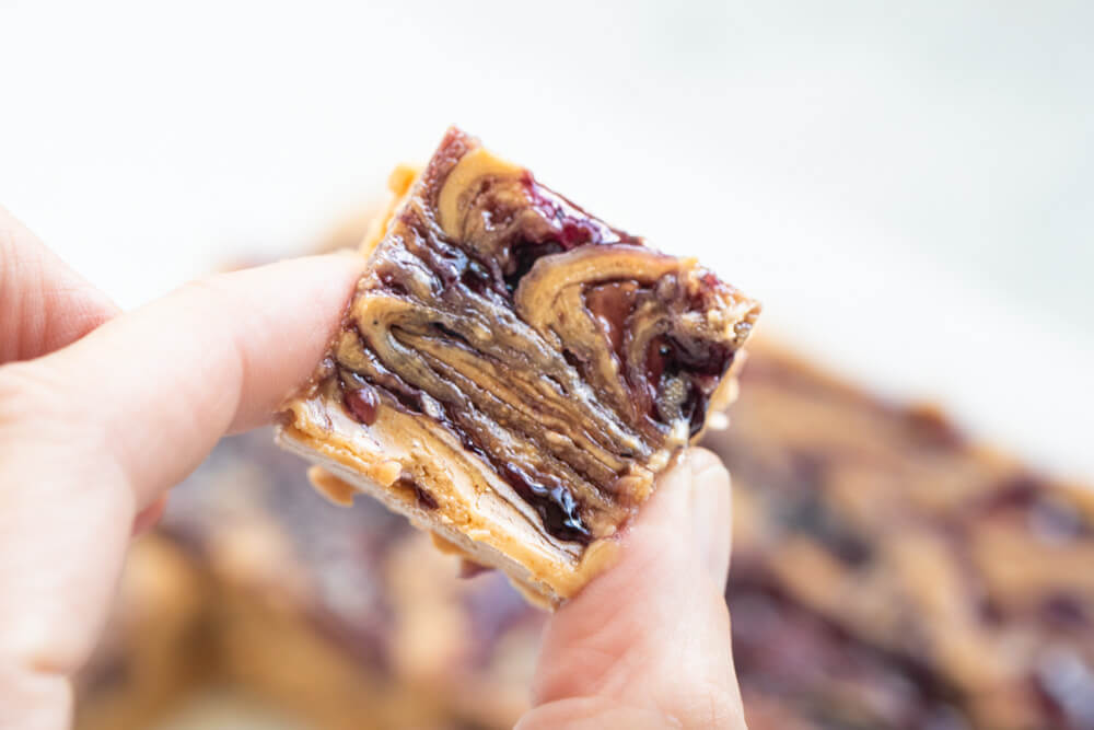 fingers holding vegan peanut nutter and jelly bars