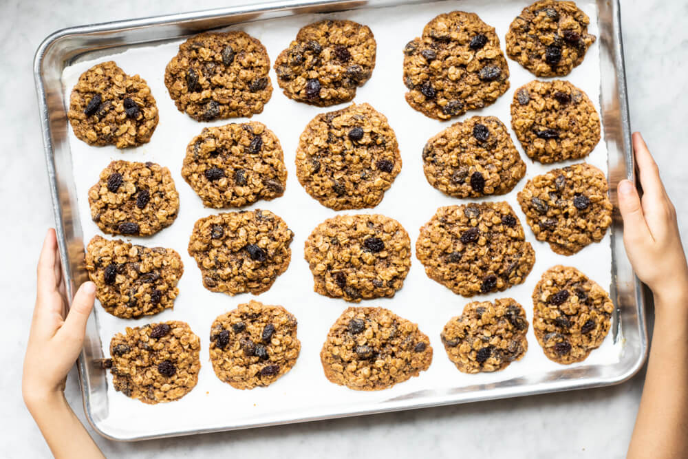hands holding silver tray of gluten free oatmeal raisin cookies