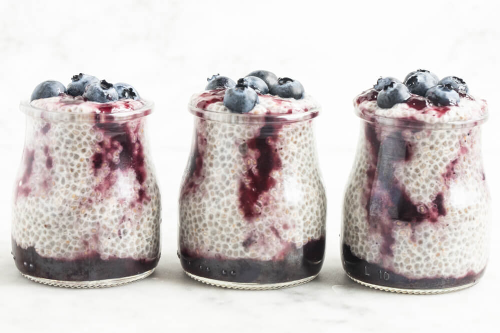 three jars of blueberry jam chia pudding on white table