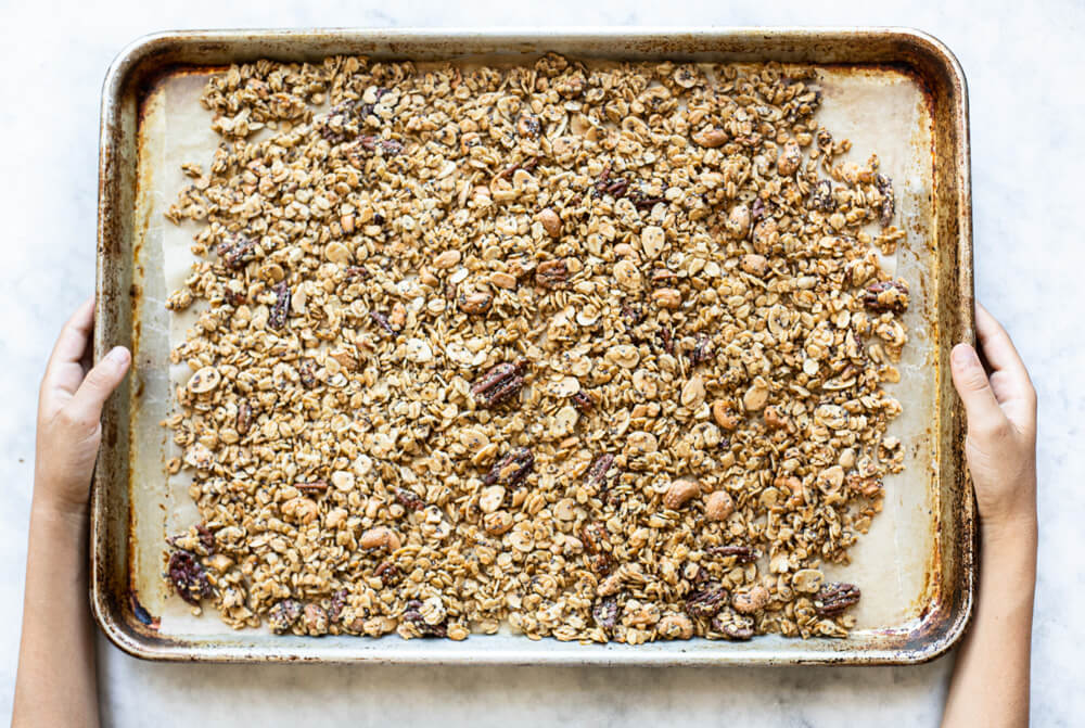 hands holding baking tray of granola
