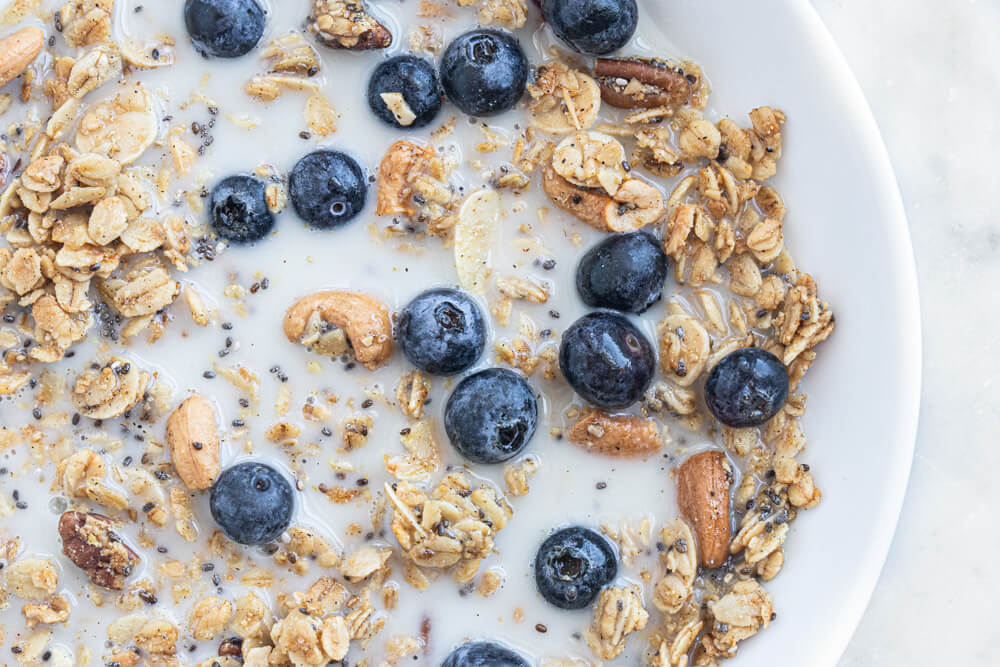 granola and milk in white bowl
