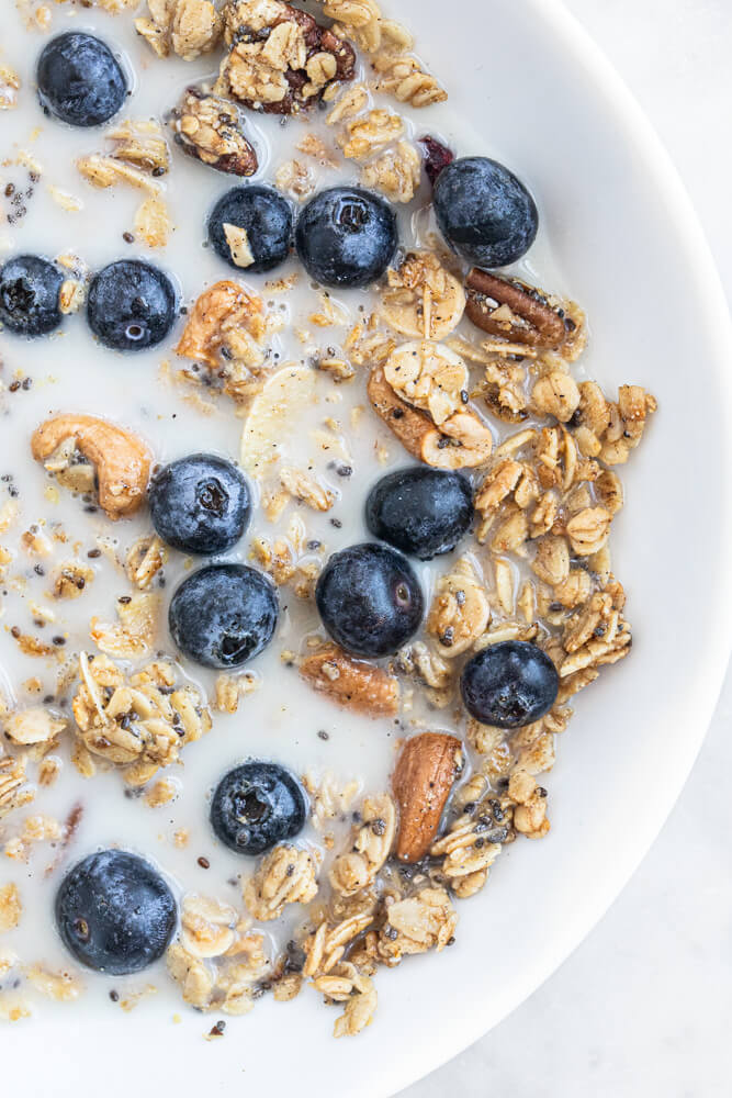 white bowl with granola and milk