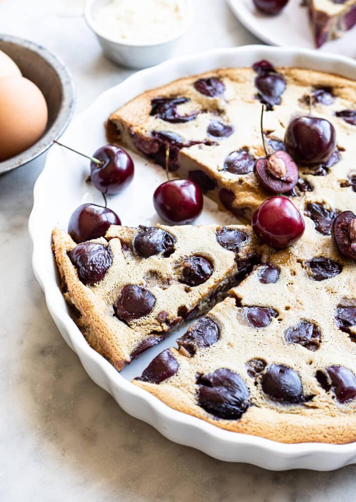 slice of cherry clafoutis in white tart pan