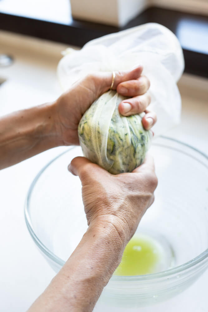 hand squeezing zucchini in nut milk bag