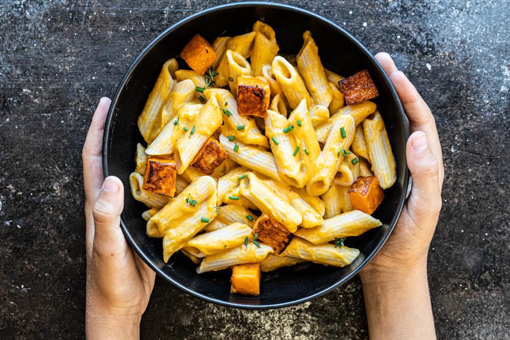 hands holding black bowl of pasta