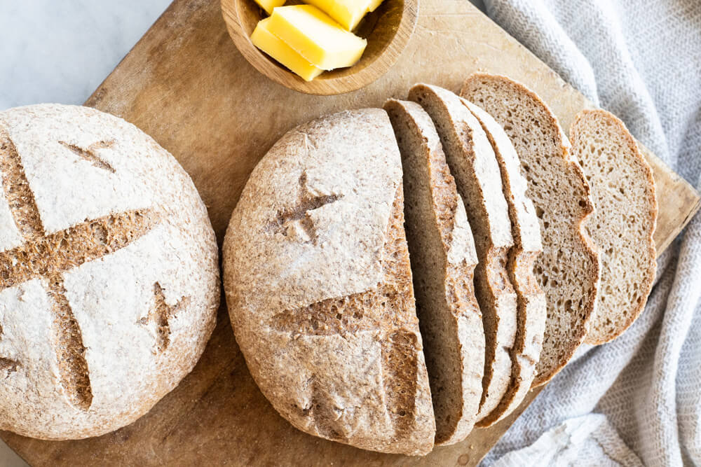 loaf of bread sliced on cutting board