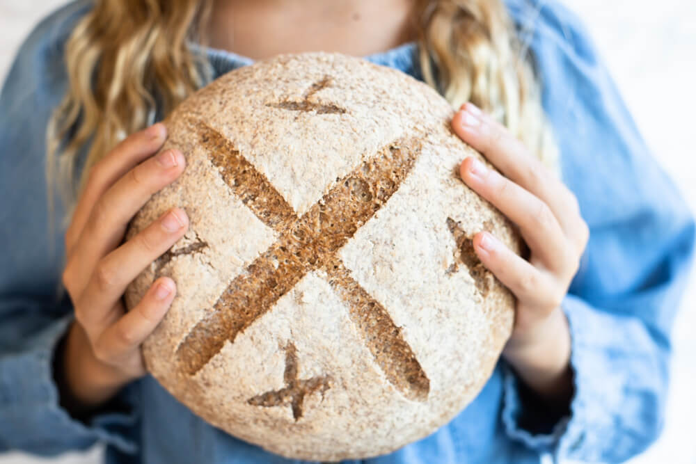loaf of gluten free bread held in child's hands