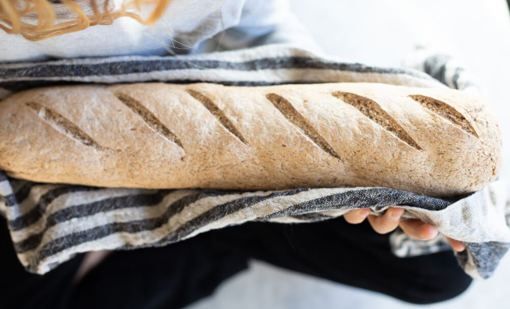 hands holding gluten free seeded sourdough