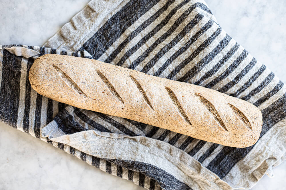 gluten free sourdough baguette on striped towel