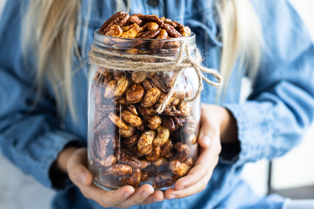 child holding glass jar of spiced nuts