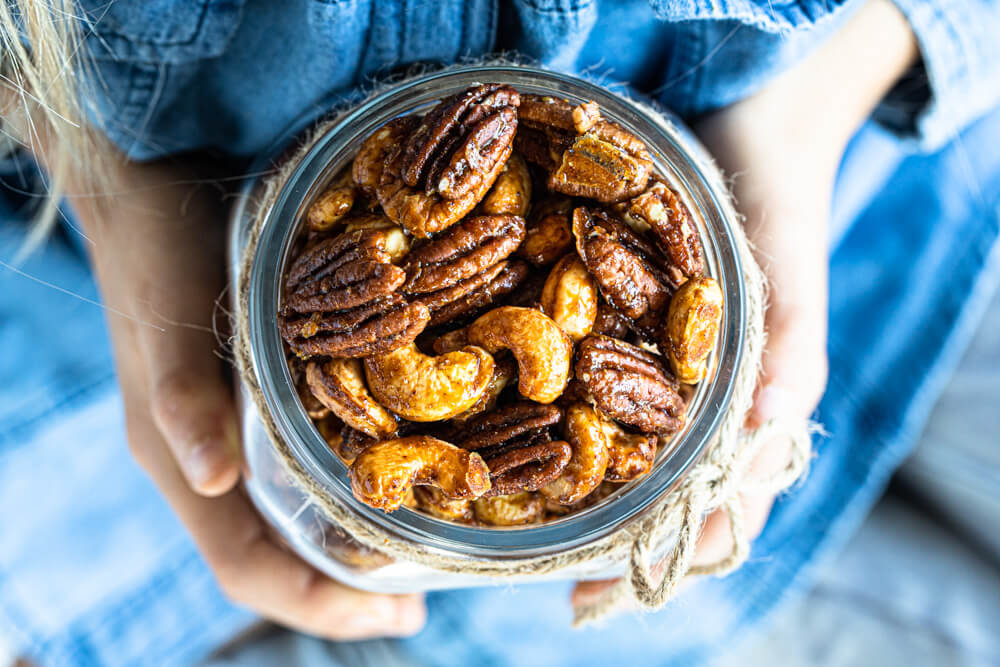 hands holding glass jar of spiced nuts