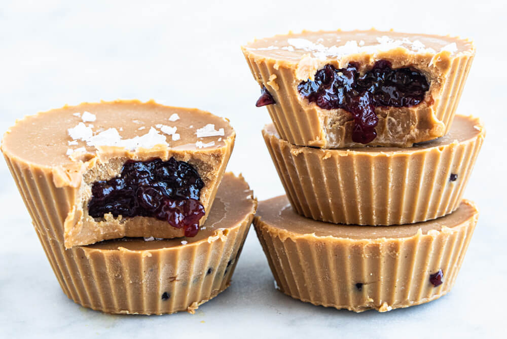 five peanut butter and jelly cups on white counter